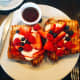 Restaurant French toast topped with fresh fruit and served with maple syrup