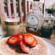 Homemade pancakes topped with fresh sliced strawberries and served with two types of maple syrup