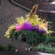 Exterior Easter Decoration with yellow forsythia and pink flowers and a purple egg