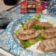 Cooked potstickers on a bed of romaine