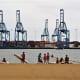 The cranes and freight containers of Puerto de la Luz across the water from Playa de las Alcaravaneras.
