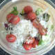 Salad leaves, grated turnip and tomato halves are seasoned and combined