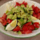Eggs with fresh avocado and tomato on lettuce