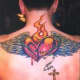 A winged flaming heart tattoo with a cross.