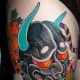 A colorful black hannya tattoo.