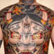 A large, symmetrical hannya mask tattoo on the back.