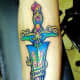 A colorful sword tattoo with text.