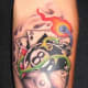 An eight ball tattoo on the forearm with other gambling items.