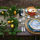 For an additional $60, you can upgrade the centerpiece for a square navy runner, a cutting board, a cheese knife set, a faux lemon garland, and two Quinn Crystal compotes. The lemon garland is featured in this picture.