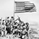 American troops celebrate the capture of Mount Suribachi. But the Japanese still held a strong position and the bloodiest fighting was yet to take place.