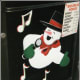 A singing snowman painted at the bottom of a door panel.