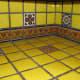 Yellow talavera tile kitchen countertop with border and single pattern tiles.