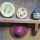 Shelf, plates, jug, painted designs on plates and jug. Hat with brim, ribbon on hat.