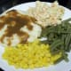Vegetable plate with potatoes and gravy, corn, green beans, and slaw