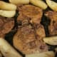 Pork chops are hot, tender and ready to serve with potatoes sprinkled with rosemary leaves.