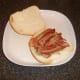 Crispy bacon is laid on steak