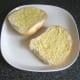 Bread roll is spread with Dijon mustard