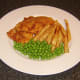 Garden peas are served with the sea bream fillets and chips