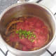 Tomatoes and chopped chilli are added to spiced onions and garlic