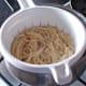 Spaghetti is drained through a colander