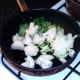 Cauliflower, pak choi and onion are added to pan with duck fat and juices
