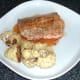 Roast cauliflower is plated with salmon