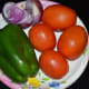 The vegetables used for making tomato and capsicum curry.