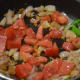 Step four: Throw in chopped tomatoes, pepper corns, a piece of nutmeg, and a cinnamon stick. Stir-fry till tomato becomes soft.