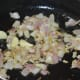 Step three: Add onions and garlic. Stir-fry until they turn transparent and pinkish.