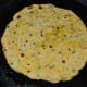 Flip when the bottom turns golden brown. Add a few drops of oil or ghee on the top. Cook the other side until golden brown. Remove and set aside on a plate. Make all the parathas like this.