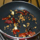 Step three: Throw in dry red chilies, tamarind, and garlic cloves. Saute for 30 seconds. Turn off the heat. Transfer the mixture to a plate.