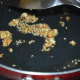 Step six: Heat 1 teaspoon oil in a small pan. Throw in chopped garlic and sesame seeds. Saute until they become golden brown.