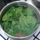 Spinach is added to simmering pasta