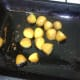 Boiled and cooled turmeric potatoes are turned in hot roasting oil