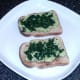 Spinach is scattered over guacamole on toast