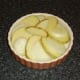 Potato and onion slices laid alternately in a baking dish