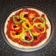 Mixed bell peppers and halved black olives are added to pizza