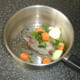 Quail, chopped vegetables and seasoning are added to a large pot
