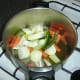 Vegetables are added to the stock pot and warmed olive oil.