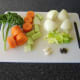 Vegetables and herbs are prepared for poaching chicken