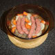 Sausages, beef and vegetables are added to casserole and seasoned