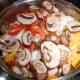 Cover the cooked chicken with peppers and onions. Add one cup of sliced mushrooms. Cover and simmer for about 5 minutes.