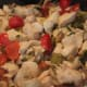 Chicken cooking with cherry peppers, garlic, scallions and mushrooms.