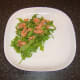 Rccket leaves (arugula) and smoked salmon are arranged on the serving plate