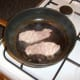 Bacon is fried in the same pan as sausage and black pudding