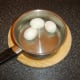 Hard boiled and peeled eggs are cooled in cold water