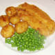 Potatoes and peas are plated alongside haddock