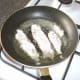 Flounder fillets are added to frying pan