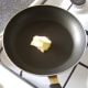 Butter is added to small, non-stick frying pan
