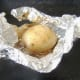 Baked potato is carefully unwrapped from foil